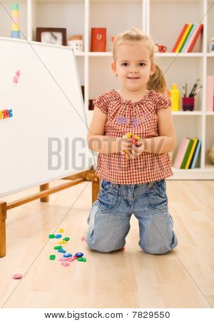 Little Girl Playing With Magnetic Board