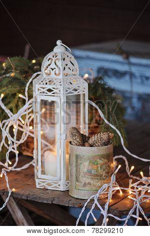 Christmas lights, lantern and box of pine cones