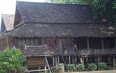 foto of reconstruction  - Reconstructed on this site in 2007 for preservation the timber house has props against the left hand end  - JPG