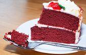 picture of red velvet cake  - Fork full of red velvet cake and a slice on a white dish - JPG
