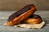 picture of eclairs  - Tasty eclairs on wooden table - JPG