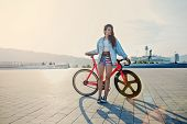picture of bicycle gear  - Pretty young brown haired woman standing with her modern pink bicycle at sunset stylish hipster girl attractive young woman win fixed gear bike posing outdoors with soft sunset light on background - JPG