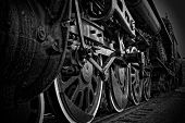 stock photo of train track  - A closeup view of the wheels of an antique steam train in black and white - JPG