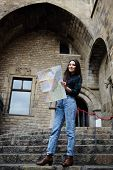 stock photo of gothic female  - Young female traveler searching right direction on city map beautiful tourist woman on vacation with a map in antique gothic citypretty young female tourist studying a map standing in gothic quarter - JPG