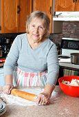 stock photo of grandma  - Senior woman or grandma rolling dough to make pies in her kitchen - JPG