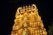 stock photo of swami  - Trinesvara Swami Temple is illuminated with thousands of lightbulbs at night in Mysore palace - JPG