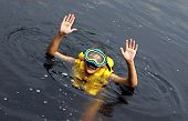 image of vest  - Young boy swimming in lake with swimming mask and swim vest