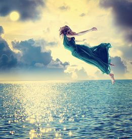 stock photo of surrealism  - Beautiful girl jumping into the blue night sky over the ocean - JPG