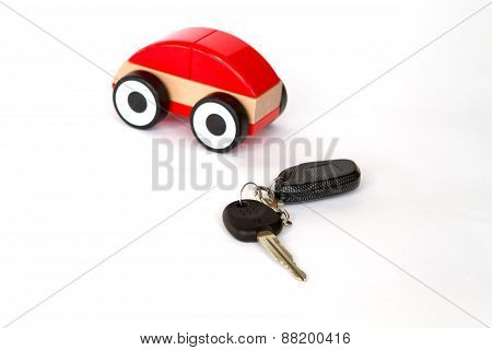 toy car red color on a white background with a remote control and key