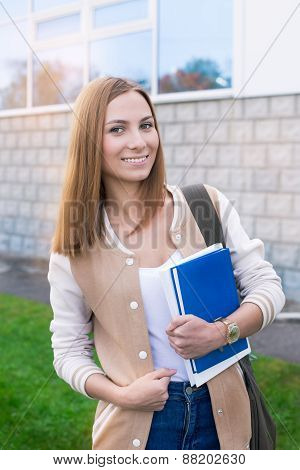 Student Standing With Book In One Hand And Smiling
