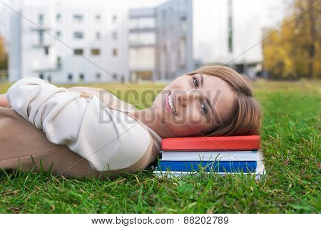 Student Lying On Green Grass And Book