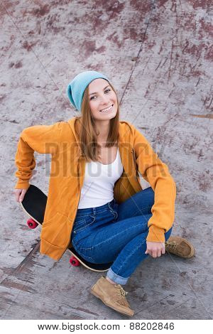 Student Sitting On Skateboard And Smiling At The Camera