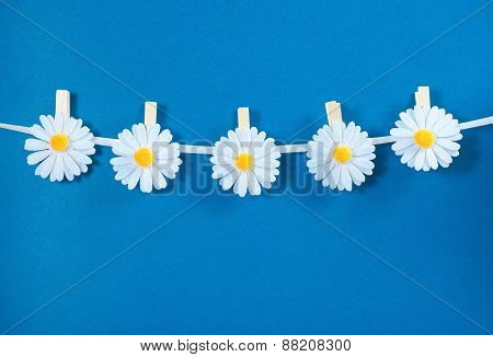 Chamomile flower clothespins decoration on blue background