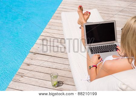 Woman working with laptop computer by the swimming pool