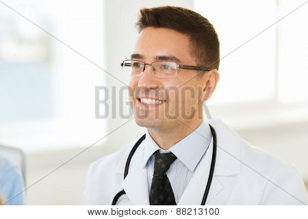healthcare, profession and medicine concept - smiling male doctor in white coat and eyeglasses at hospital