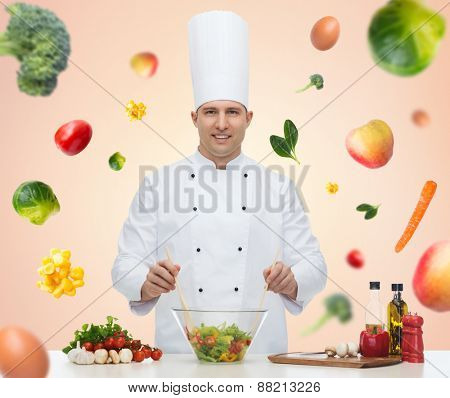 profession, vegetarian diet, food and people concept - happy male chef cooking vegetable salad over beige background with falling vegetables