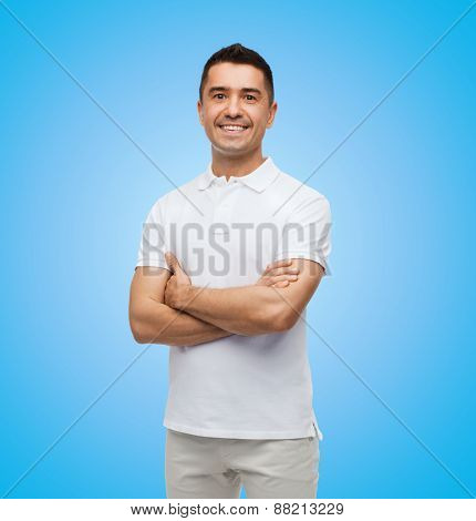 happiness and people concept - smiling man in white t-shirt with crossed arms over blue background