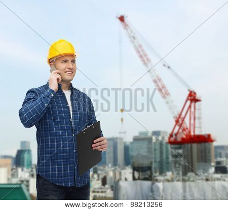construction, building, people, technology and maintenance concept - smiling male builder or manual worker in helmet with clipboard calling on smartphone  over city construction site background