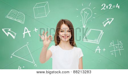 advertising, school, education, childhood and people - smiling little girl in white t-shirt showing ok sign over green board with doodles background