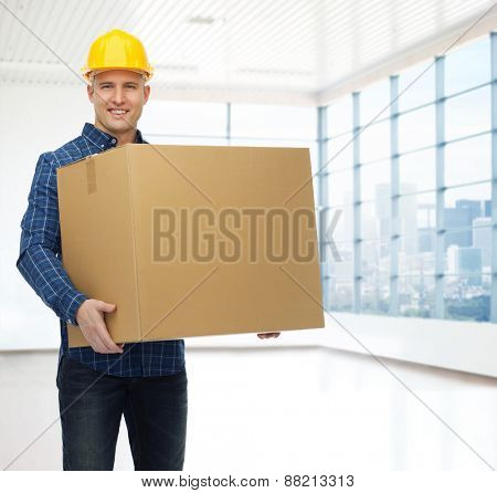 repair, construction, building, people and maintenance concept - smiling male builder or manual worker in helmet carrying big cardboard box over empty flat background