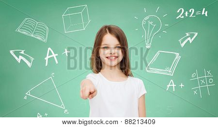 advertising, gesture, school, education and people - smiling little girl in white blank t-shirt pointing finger on you over green board background with doodles