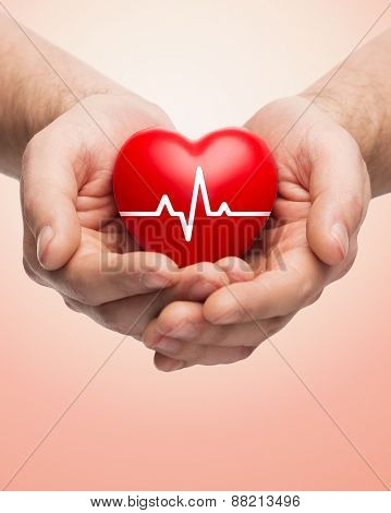 family health, charity and medicine concept - close up of hands holding red heart with cardiogram over beige background