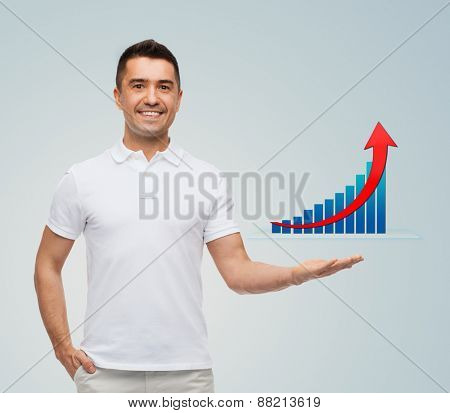 business, statistics, economics, success and people concept - smiling man showing growing chart over gray background