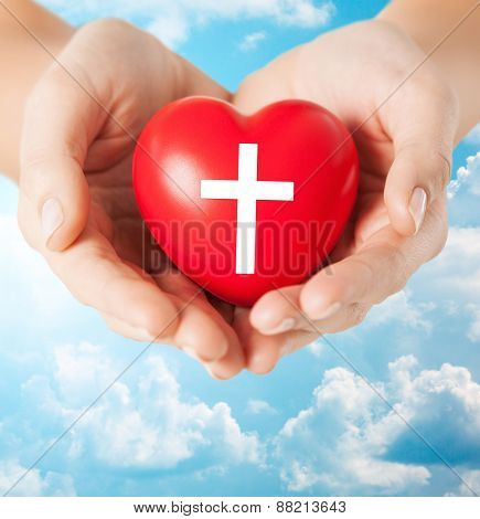 religion, christianity and charity concept - close up of female hands holding red heart with christian cross symbol over blue sky and clouds background