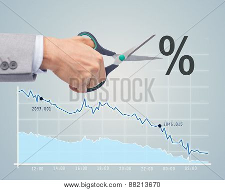 business, people, default, financial and economical crisis concept - close up of businessman hand with scissors cutting percentage sign over chart and gray background