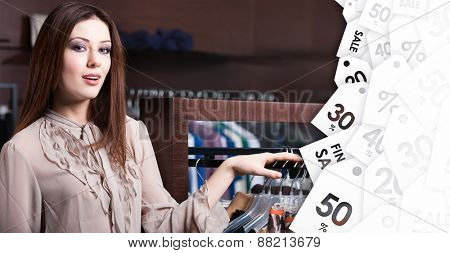 Attractive woman is in the store with wide range of clothes on sale
