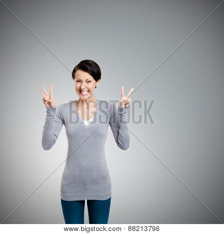 Smiley woman shows victory sign with two hands, isolated on white