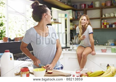 Two Female Friends Preparing Breakfast At Home Together