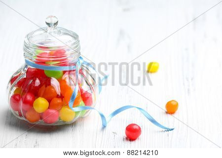 Colorful candies in jar on wooden background
