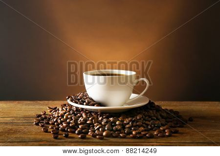 Cup of coffee with grains on wooden table on dark background