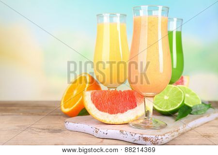 Fresh summer cocktails with fruits on wooden table on bright blurred background