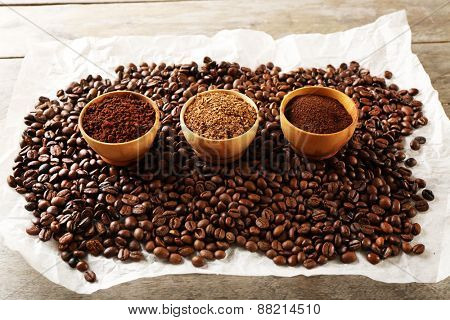 Coffee beans on crumpled parchment on wooden table, closeup