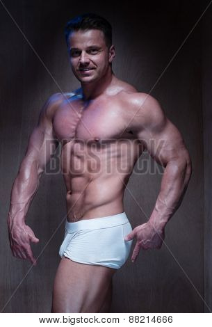 Muscular Man Wearing Tight White Boxer Shorts Looking Down and To the Side in Dimly Lit Room