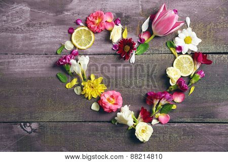 Heart of beautiful flowers, on wooden table