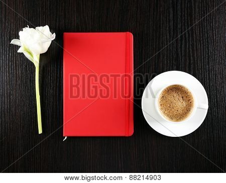 Cup of coffee with notebook and fresh flower on wooden table background