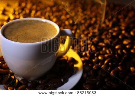 Cup of coffee with grains, closeup