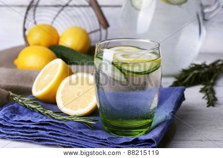 Fresh water with lemon and cucumber in glassware on napkin on wooden table, closeup