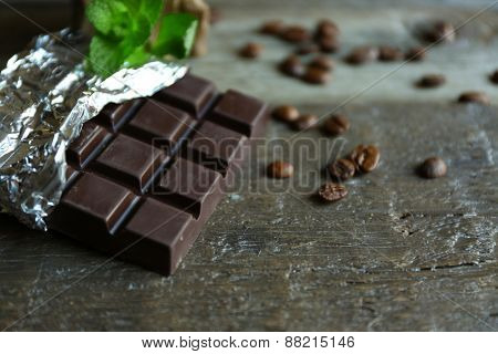 Chocolate with mint and coffee beans on wooden background