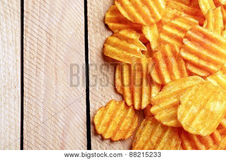 Delicious potato chips on wooden table close-up