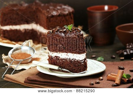 Delicious chocolate cake on table on brown background