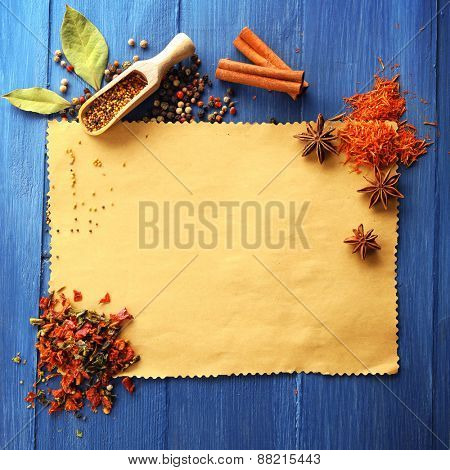 Different kinds of spices on paper sheet on wooden background