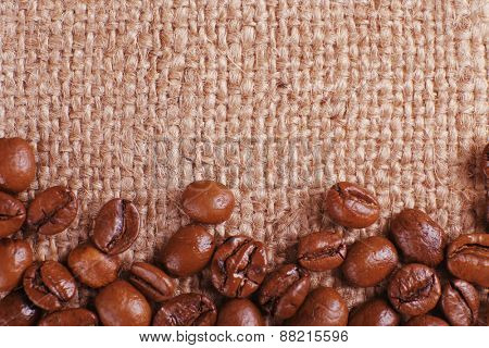 Frame of coffee beans on sackcloth background