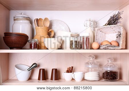 Kitchen utensils and tableware on shelves