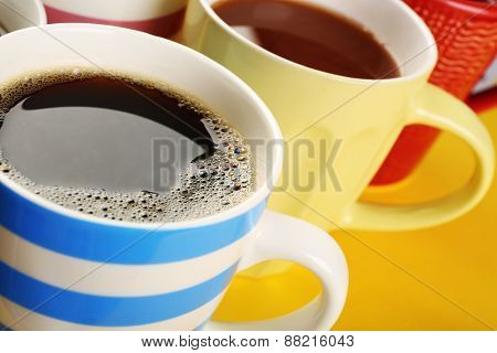 Many cups of coffee on color table, closeup