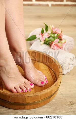 Woman washing beautiful legs in bowl. Spa procedure concept