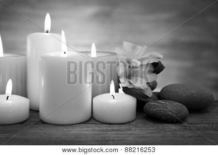 Beautiful composition with candles and spa stones on table in black and white
